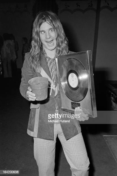 English singer Ozzy Osbourne holding a flower pot and a gold disc for sales of over one hundred thousand copies of Black Sabbath's album 'Paranoid'...