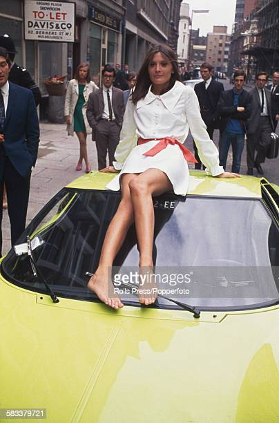 English singer Sandie Shaw sits barefoot on the roof of a Lamborghini Miura car during a press launch for her first fashion collection outside her...