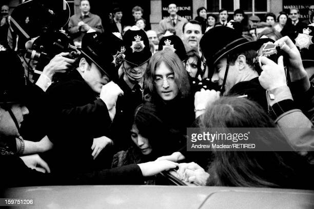 English singer songwriter and musician John Lennon and his girlfriend Yoko Ono leave Marylebone Magistrates' Court in London after their hearing on...