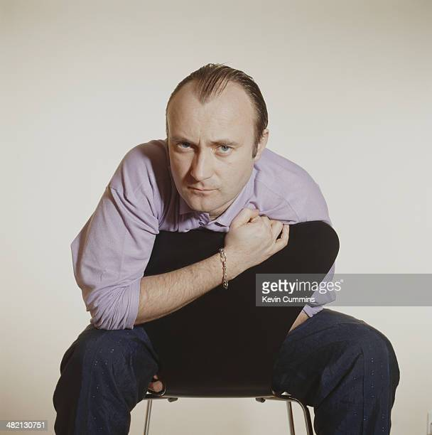 English singer songwriter and musician Phil Collins astride an Arne Jacobsenstyle chair 12th February 1990