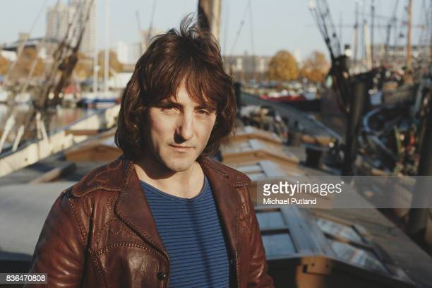 English singersongwriter and former Wings and Moody Blues guitarist Denny Laine posed wearing a leather jacket outside near an harbor 1981