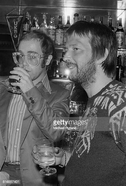 English singersongwriter Elton John with rock guitarist and singer Eric Clapton at a special party to mark Clapton 's return to recording and live...