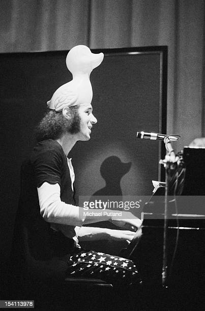 English singersongwriter Neil Innes performing with a rubber duck on his head at a concert by English pop poetry and comedy group Grimms at Watford...