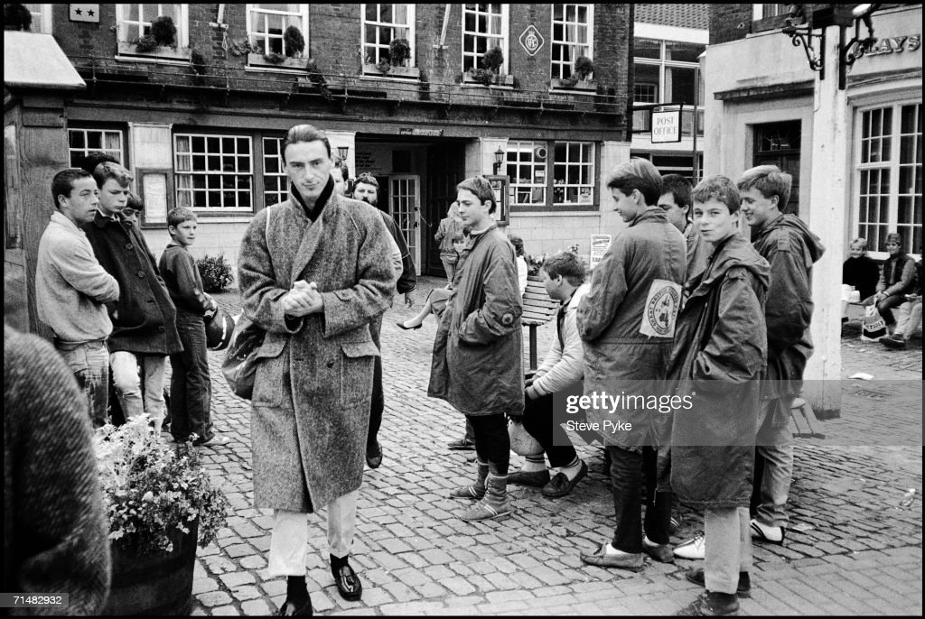 English singer-songwriter Paul Weller is watched by a group of mods in the courtyard of a pub in Oxford, 6th October 1984.