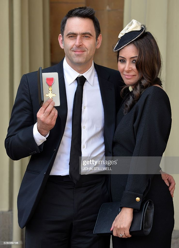 English snooker player Ronnnie O'Sullivan (L) stands with his fiancee British actress Laila Rouass, as he poses with his medal after being appointed an Officer of the Order of the British Empire (OBE), at an investiture ceremony at Buckingham Palace in London on May 6, 2016. / AFP / POOL / John Stillwell