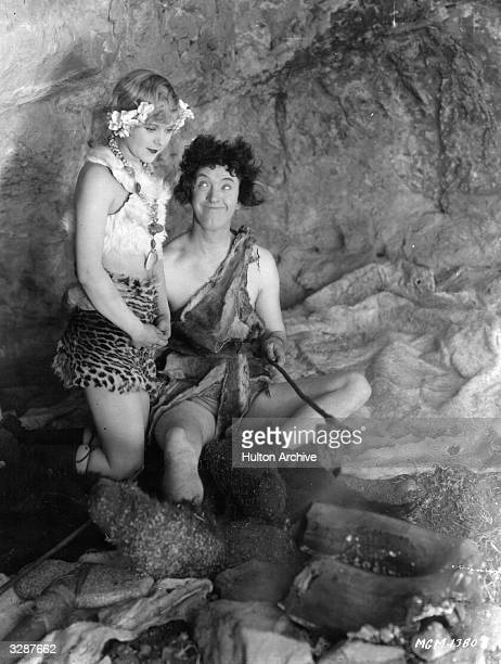 English stage and screen comedian Stan Laurel plays a caveman in 'Flying Elephants' opposite actress Edna Marion