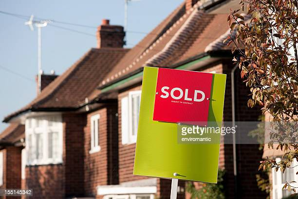 English suburban house with 'sold' sign.