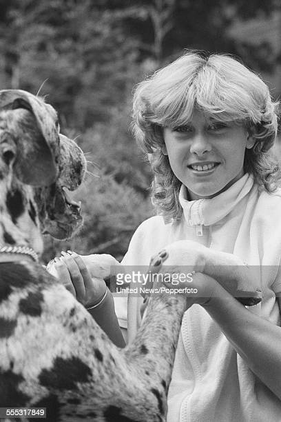 English swimmer and television presenter Sharron Davies pictured with a Great Dane dog in London on 22nd August 1983