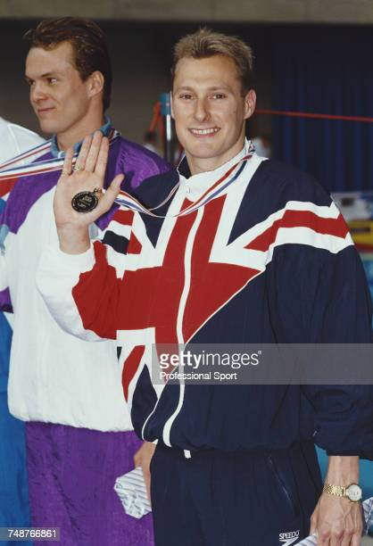 English swimmer Nick Gillingham stands on the podium after finishing in first place to win the gold medal for the Great Britain team in the Men's 200...