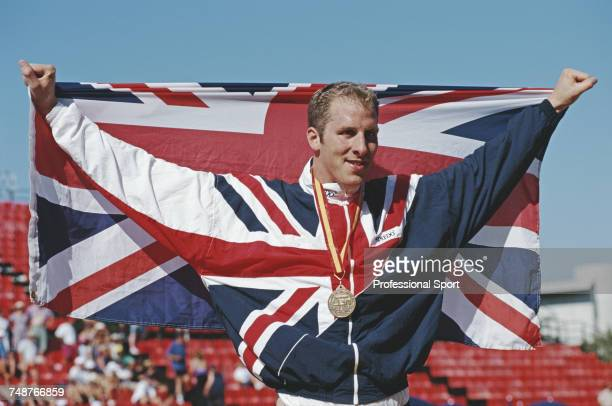 English swimmer Paul Palmer celebrates with the union flag of Great Britain after winning the gold medal in the Men's 200 metres freestyle event at...