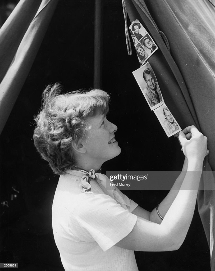 English teenager Heather Charlton pinning photographs of her favourite film stars including Alan Ladd and Gary Cooper to the flap of her tent at the...