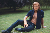 English tennis player John Lloyd posed wearing an unbuttoned dark blue shirt and jeans in 1977 Photo by Leo Mason/Popperfoto/Getty Images