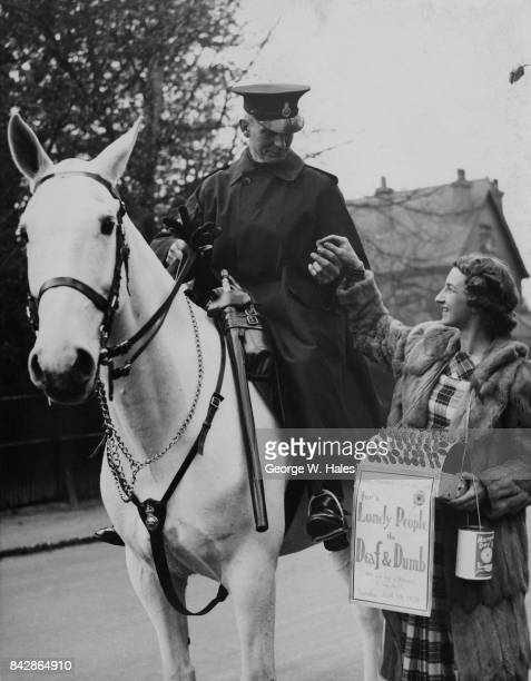 English tennis player Mary Hardwick sells a flag to a policeman at Wimbledon on Marigold Day to collect money for the Royal Association for the Deaf...