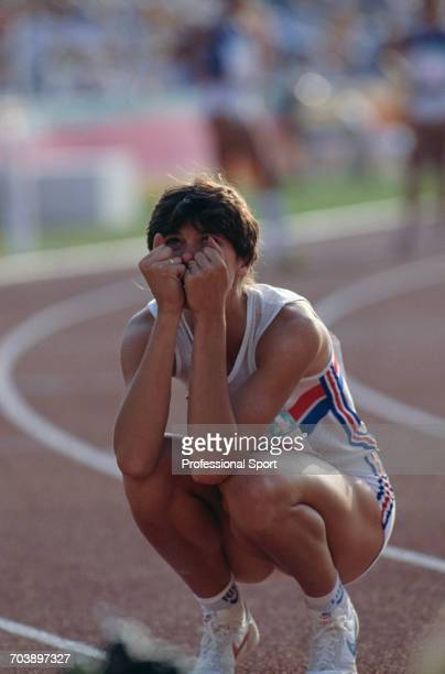 English track athlete Kathy SmallwoodCook crouches down on the track after crossing the finish line on 4th place for Great Britain in the final of...