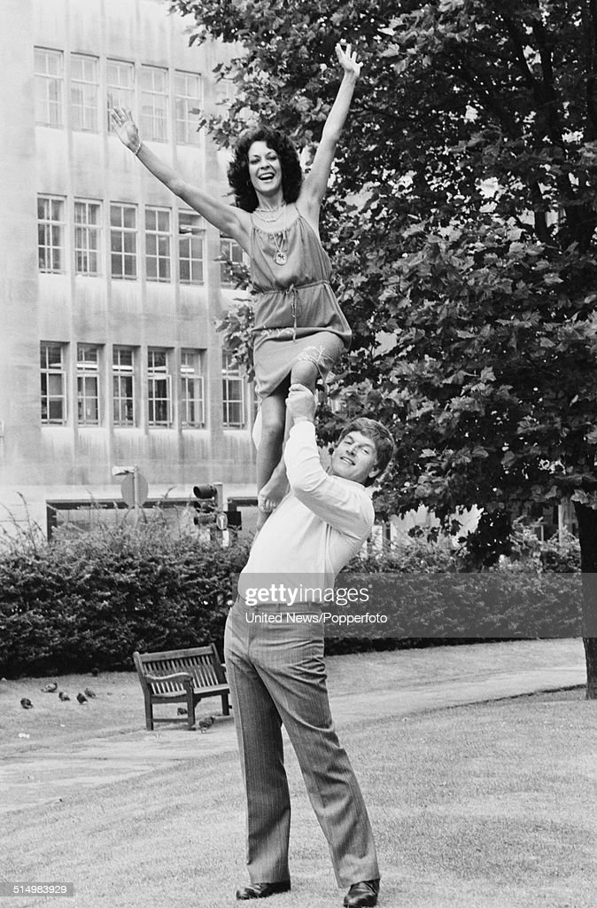 English weightlifter and actor Dave Prowse posed lifting a young woman over his head in a London square on 23rd July 1981.