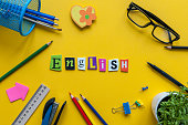 English word of carved letters on yellow background with office or school supplies,English language learning concept.