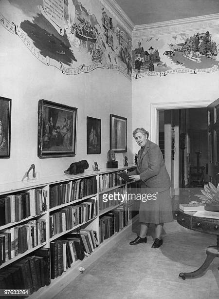 English writer Dame Agatha Christie puts back in March 1946 a book on a shelf in the library of her home Greenway House in Devonshire The frescoes on...
