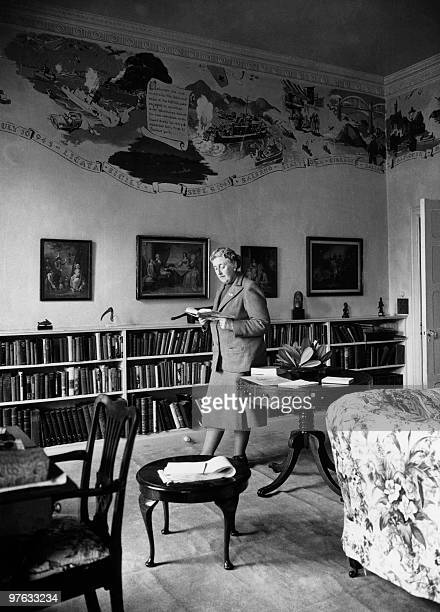 English writer Dame Agatha Christie reads in March 1946 a book in the library of her home Greenway House in Devonshire The frescoes on the wall...