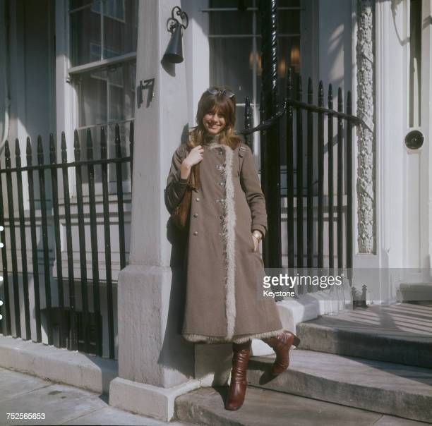 EnglishAustralian singer Olivia NewtonJohn wearing a threequarter length coat and boots London circa 1970