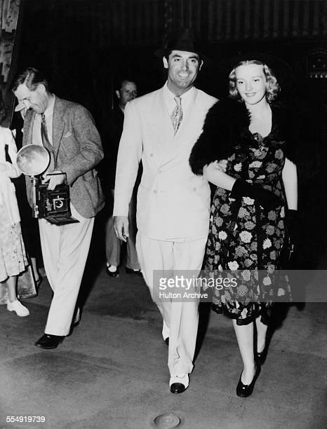Englishborn actor Cary Grant and American actress and model Phyllis Brooks leaving a theatre circa 1938