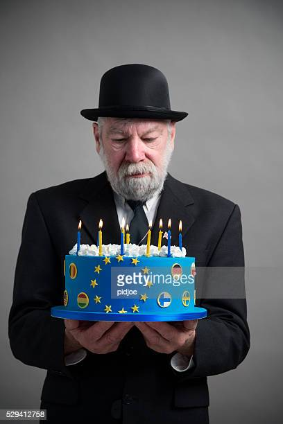 Englishman with bowler hat with EU cake with candles