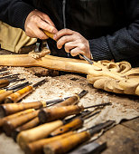 An engraver is carving a wood frame