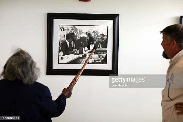 Enid Curtis Pinkney Founding President and CEO of the Historic Hampton House Community Trust shows Eddy Ramos a picture of Malcolm X taking a...