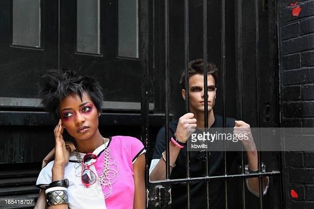 Geheimnisvolle mixed race girl mit Freund am gate bars