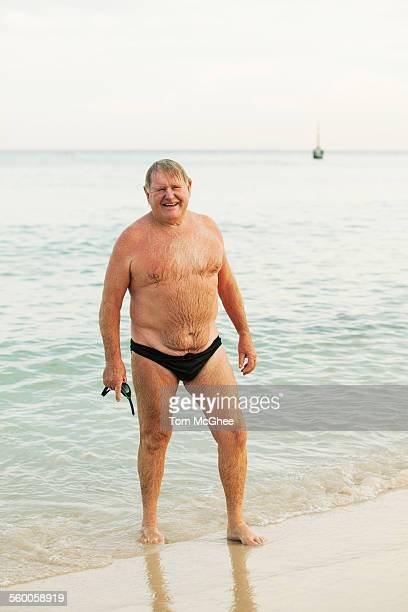 enior male wearing bathers standing at beach