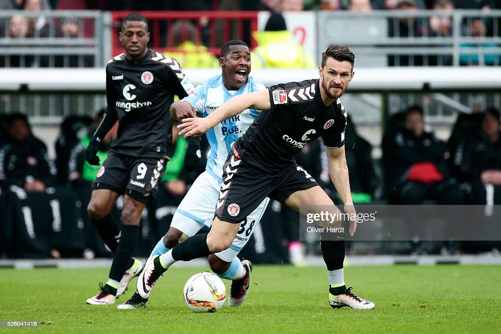 Enis Alushi (R) of Hamburg and Florent Romuald Lacazette (C) of Muenchen compete for the ball during the Second Bundesliga match between FC St. Pauli and 1860 Muenchen at Millerntor Stadium on April 29, 2016 in Hamburg, Germany.