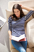 Shot of a relaxed woman reading a book while lying on sofa at home.