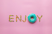 Enjoy word made of sprinkles and blue donut on pink background. Creative color concept.