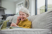 Senior woman is curled up on the sofa in her home with a cup of tea while she enjoys a phonecall on a smartphone.