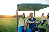 Two young couples enjoying time on a golf course.