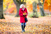 Senior woman is enjoying an independent walk through the autumn woods. She is collecting leaves and enjoying the views.