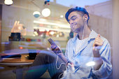 Young handsome man with smartphone and earbuds relaxing in cafe and enjoying his favorite music
