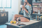 Close-up of beautiful young mixed race woman holding coffee cup and talking on the mobile phone with smile while sitting on the kitchen desk