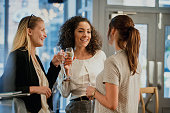 Three businesswomen are enjoying glasses of wine at a bar after work.