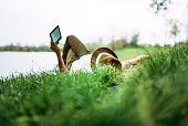 Enjoying e-book near the lake. Girl lying in the grass.