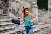 Portrait of a smiling young woman exploring the city with bicycle.