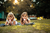 Girls lying on a grass and eating ice cream.