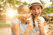 Two happy Indonesian girl eating ice-creams outdoors