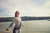 Woman with arms wide open enjoying in sunshine by the river. Enjoying life and breathing fresh air with eyes closed.