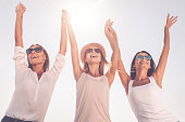 Low angle view of three beautiful young women holding hands and raising their arms up