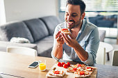Hungry young man eating sandwich at home