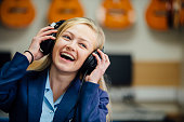 Teen student is enjoying listening to music on some headphones in her school music lesson. She is swaying to the beat and is laughing.