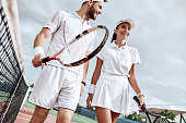 Enjoying spending time on the court. Beautiful young couple walking on the tennis court with smile.