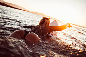 A girl swimming and getting ready to surf in sunset