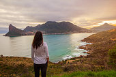 A tourist stands at a lookout point enjoying a beautiful view of the mountains and bay of Hout Bay, Cape Town