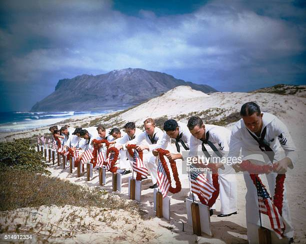 Enlisted men of the Naval Air Station at Kaneohe Hawaii place leis on the graves of their comrades killed in the Japanese attack on Pearl Harbor last...